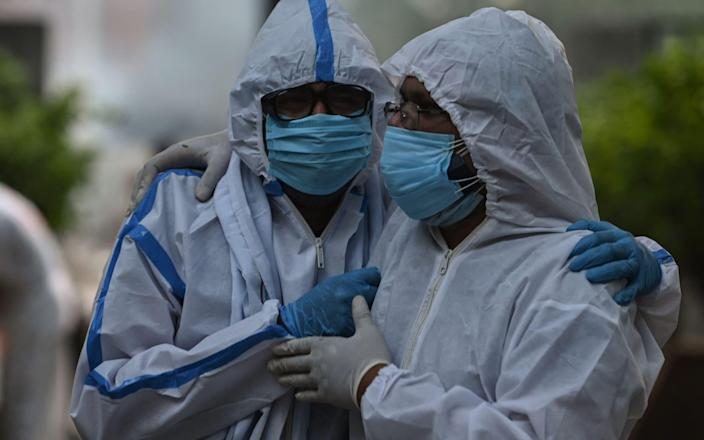 At a crematorium in New Delhi, relatives wear PPE for the funeral of a person who died of coronavirus - ARUN SANKAR/AFP