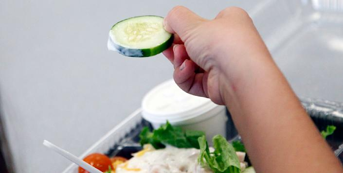 A Eastside Elementary student holds a fresh cucumber slice dipped in ranch dressing ready for consuming as part of one of the nutritious lunches prepared for the students at the Clinton, Miss., school Wednesday, Sept. 12, 2012. The leaner, greener school lunches served under new federal standards are getting mixed grades from students. (AP Photo/Rogelio V. Solis)