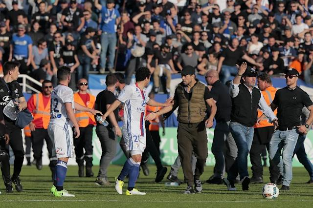 A Bastia's official (C-R) argues with Lyon's Brazilian defender Rafael da Silva (C-L) during scuffles at half-time between some of Lyon's players and Bastia's officials, during the French L1 football match Bastia vs Lyon on April 16, 2017 (AFP Photo/PASCAL POCHARD-CASABIANCA)