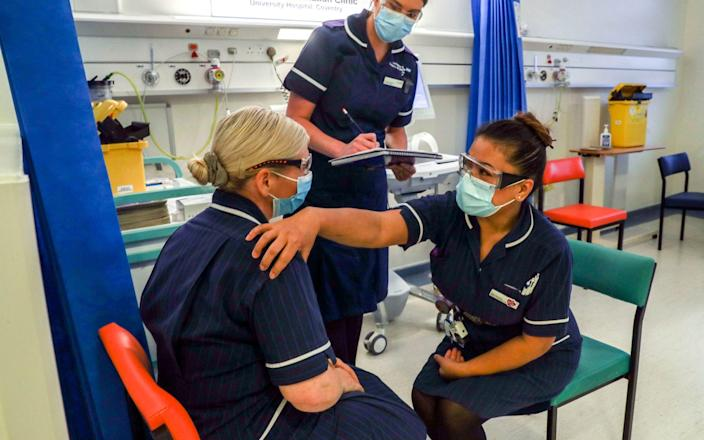 Matron May Parsons (right) is assessed by Victoria Parker (centre) during training in the Covid-19 Vaccination Clinic at the University Hospital in Coventry - PA