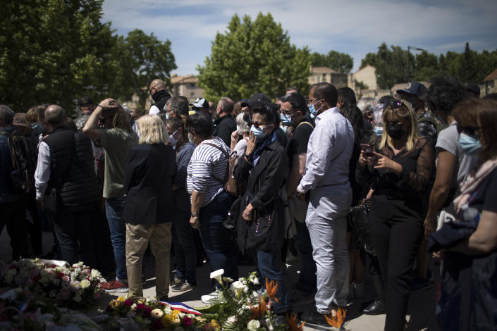 Police officers and civilians lay flowers at a police station in Avignon, southern France, Sunday, May 9, 2021. Police officers and civilians gathered to commemorate the death of a police officer who was killed Wednesday at a known drug-dealing site in the southern France city of Avignon. (AP Photo/Daniel Cole)
