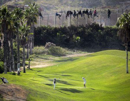 A golfer hits a tee shot as African migrants sit atop a border fence during an attempt to cross into Spanish territories between Morocco and Spain's north African enclave of Melilla in this October 22, 2014 file photo. REUTERS/Jose Palazon/Files