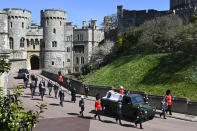 Britain's Prince Charles, from front left, Princess Anne, Prince Andrew. Prince Edward, Prince William, Peter Phillips, Prince Harry, Earl of Snowdon, Tim Laurence and Queen Elizabeth II, in car at rear, follow the coffin as it makes it's way past the Round Tower during the funeral of Britain's Prince Philip inside Windsor Castle in Windsor, England Saturday April 17, 2021. (Leon Neal/Pool via AP)