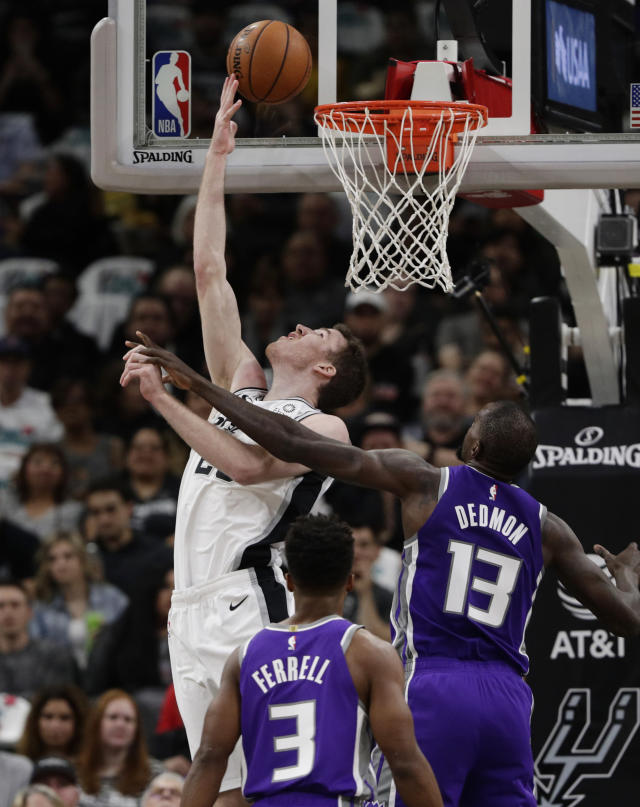San Antonio Spurs center Jakob Poeltl, upper left, scores past Sacramento Kings center Dewayne Dedmon (13) during the first half of an NBA basketball game in San Antonio, Friday, Dec. 6, 2019. (AP Photo/Eric Gay)