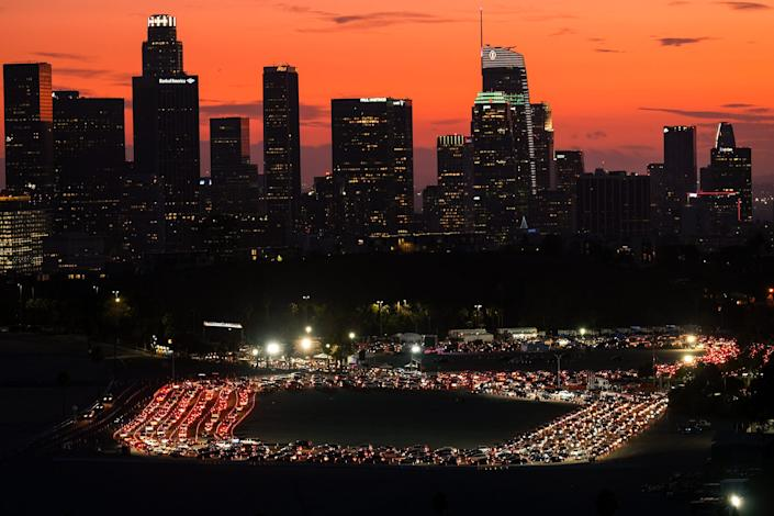 Motorists wait in lines on Monday night at a COVID-19 testing site in the parking lot of Dodger Stadium in Los Angeles.