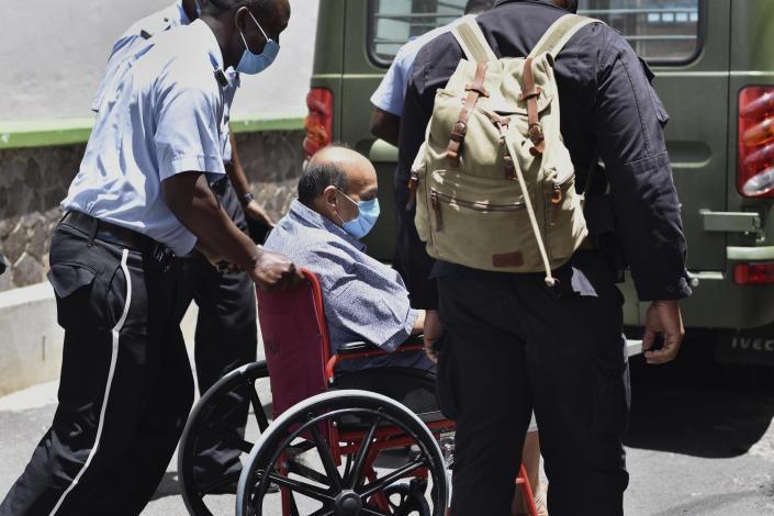 Antigua and Barbuda businessman Mehul Choksi is taken in a wheelchair to the magistrate's court by police in Roseau, Dominica, Friday, June 4, 2021. Choksi is wanted in his native India on a string of charges that include corruption, money laundering and criminal conspiracy. The fugitive was arrested May 24 on the neighboring island of Dominica accused of illegal entry. (AP Photo/Clyde Jno Baptiste)