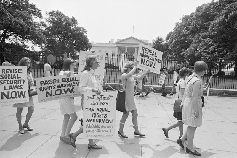Members of the National Organization for Women demonstrate outside the White House. They wear chains decorated with flowers, and are asking for passage of the Equal Rights Amendment.
