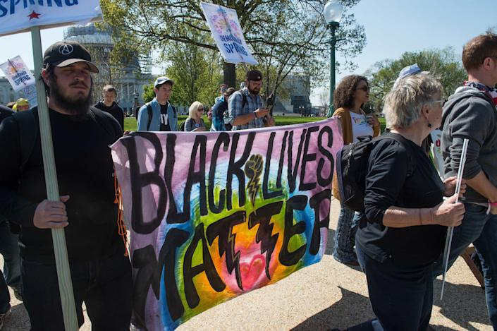 Activists of the grassroots Democracy Spring movement carry signs during a march near the Capitol on April 14, 2016.