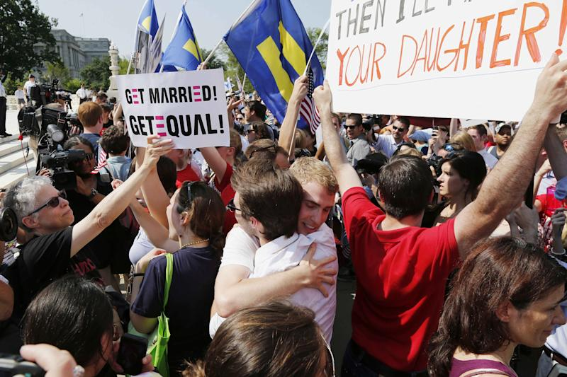 Supporters of gay marriage embrace outside the U.S. Supreme Court in Washington, Wednesday, June 26, 2013, after the court cleared the way for same-sex marriage in California by holding that defenders of California's gay marriage ban did not have the right to appeal lower court rulings striking down the ban. (AP Photo/Charles Dharapak)