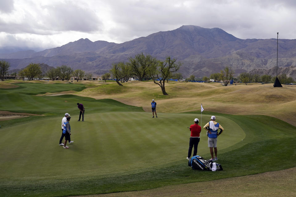 Tony Finau, top left, putts on the first hole during the third round of The American Express golf tournament on the Pete Dye Stadium Course at PGA West Saturday, Jan. 23, 2021, in La Quinta, Calif. (AP Photo/Marcio Jose Sanchez)