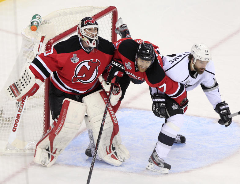New Jersey Devils' Henrik Tallinder, center, struggles with Los Angeles Kings' Justin Williams near goalie Martin Brodeur in the second period during Game 5 of the NHL hockey Stanley Cup finals, Saturday, June 9, 2012, in Newark, N.J.. (AP Photo/Frank Franklin II)