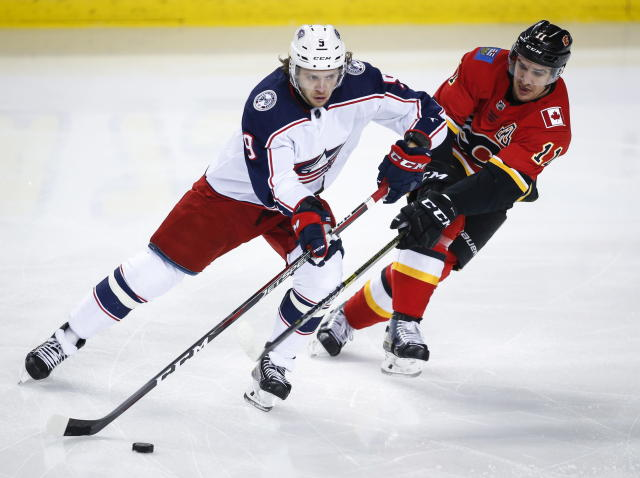 Columbus Blue Jackets' Artemi Panarin, left, keeps Calgary Flames' Mikael Backlund away from the puck during the first period of an NHL hockey game in Calgary, Alberta, Tuesday, March 19, 2019. (Jeff McIntosh/The Canadian Press via AP)
