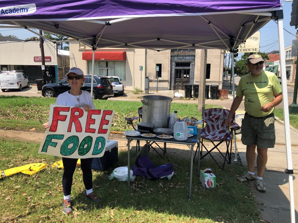 Joyce and Dave Thomas offer free jambalaya, cooked up by one of their neighbors, along the Carrollton streetcar tracks in New Orleans on Thursday, Sept. 2, 2021. Much of the city was without power and many restaurants and individuals were trying to help the community with free food. (AP Photo/Kevin McGill)
