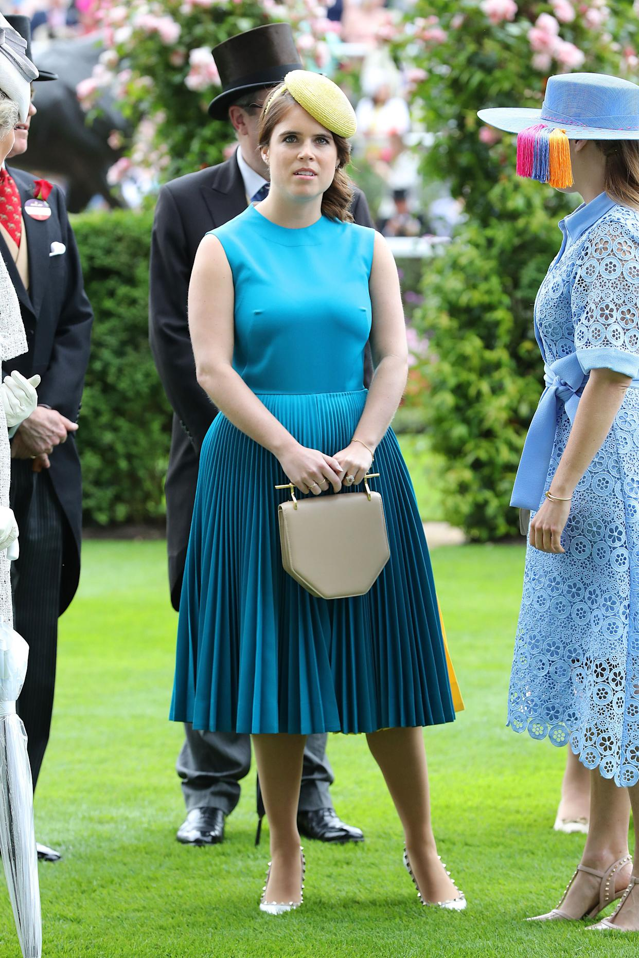 Princess Eugenie paired her teal blue dress with a bright yellow hat and a neutral clutch. (Photo: Chris Jackson via Getty Images)