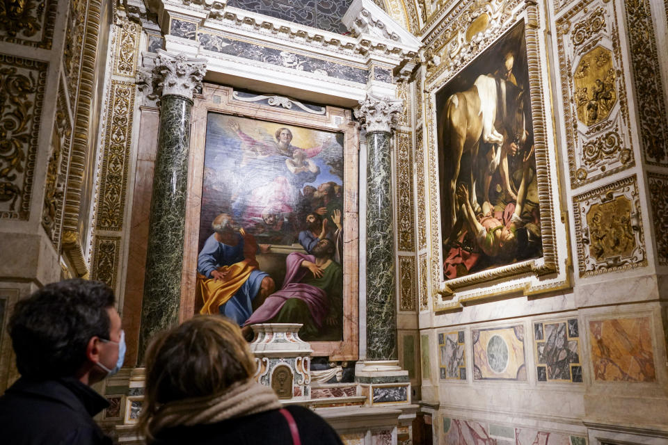 "Visitors admire the ""Conversion (of St. Paul) on the Way to Damascus"", 1601, right, by Renaissance master Michelangelo Merisi, known as Caravaggio of 1601, flanking ""The Assumption of the Virgin"", 1601, by Annibale Carracci, inside the Cerasi Chapel of Santa Maria del Popolo church, Rome, Friday, Dec. 11, 2020. Like elsewhere in Europe, museums and art galleries in Italy were closed this fall to contain the spread of COVID-19, meaning art lovers must rely on virtual tours to catch a glimpse of the treasures held by famous institutions such as the Uffizi in Florence and the Vatican Museums in Rome. However, some exquisite gems of Italy's cultural heritage remain on display in real life inside the country's churches, some of which have collections of renaissance art and iconography that would be the envy of any museum. (AP Photo/Andrew Medichini)"