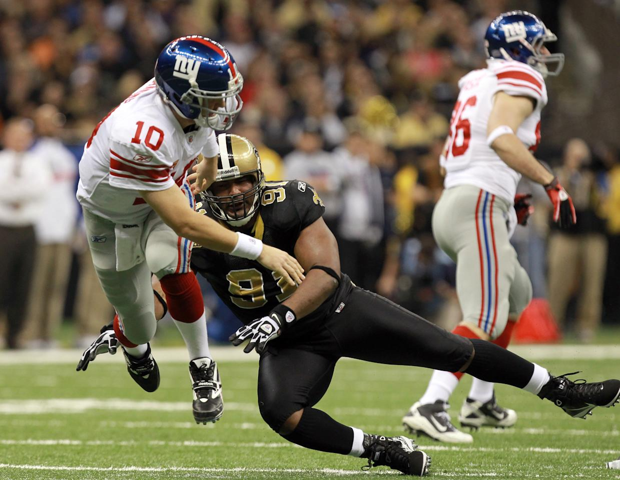 NEW ORLEANS, LA - NOVEMBER 28:  Quarterback Eli Manning #10 of the New York Giants throws the ball as he is hit by Will Smith #91 of the New Orleans Saints in the first half at Mercedes-Benz Superdome on November 28, 2011 in New Orleans, Louisiana.  (Photo by Ronald Martinez/Getty Images)