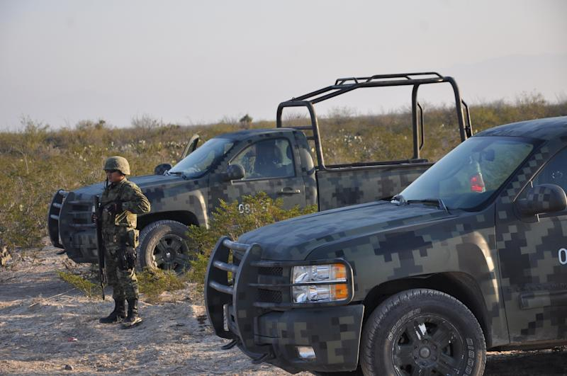 An army soldier stands guard on a dirt road leading to a ranch near the town of Mina, in northern Mexico, Monday, Jan. 28, 2013. At least eight bodies were found in a well near this ranch on Sunday near the site where 20 people went missing late last week, including members of a Colombian-style band, according to a state forensic official. Officials could not confirm whether the bodies belonged to 16 members of the band Kombo Kolombia and their crew, who were reported missing late last week after playing a private show in a bar in the neighboring town of Hidalgo north of Monterrey. (AP Photo/Emilio Vazaquez)