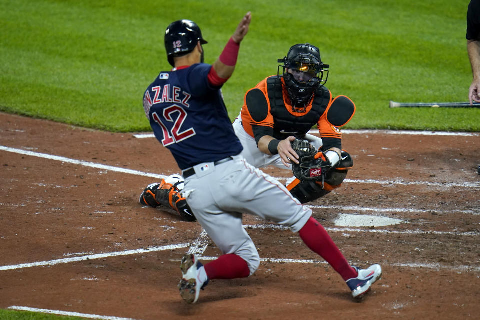 Baltimore Orioles catcher Chance Sisco, right, prepares to tag out Boston Red Sox's Marwin Gonzalez at home during the fourth inning of a baseball game, Saturday, April 10, 2021, in Baltimore. Gonzalez was trying to score on a hit by Christian Arroyo. (AP Photo/Julio Cortez)