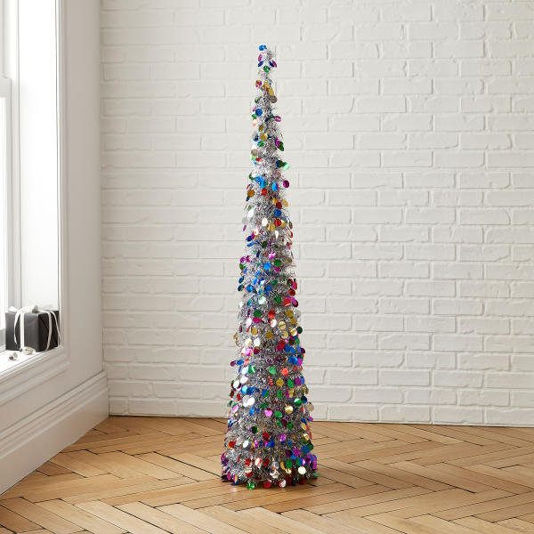 This undated photo shows West Elm's slim pop-up cone tree, clad in silver tinsel and dressed in multicolored paillettes. It's a good size for a small apartment or entryway. (West Elm via AP)