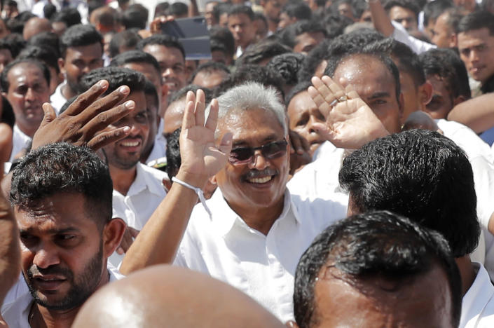 Sri Lanka's newly elected president Gotabaya Rajapaksa greets people as he leaves after taking the oath of office during the swearing in ceremony held at the 140 B.C Ruwanweli Seya Buddhist temple in ancient kingdom of Anuradhapura in northcentral Sri Lanka Monday, Nov. 18, 2019. The former defense official credited with ending a long civil war was Monday sworn in as Sri Lanka's seventh president after comfortably winning last Saturday's presidential election. (AP Photo/Eranga Jayawardena)