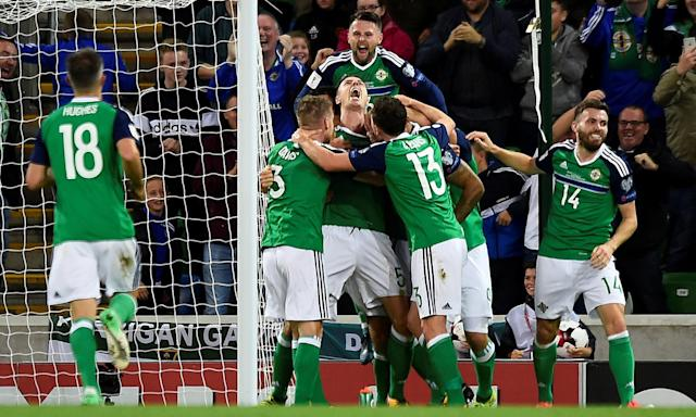Jonny Evans is engulfed by his Northern Ireland team-mates after scoring against the Czech Republic.