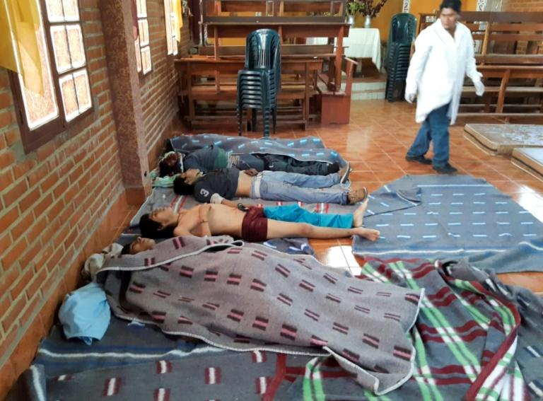 A medic looks at the bodies of five people killed during clashes between Bolivian security forces and supporters of ex-president Evo Morales in Sacaba, Chapare province, Cochabamba department on November 15, 2019