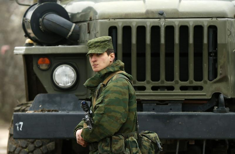 A uniformed man, believed to be Russian serviceman, stands guard near a Ukrainian military base outside the city of Sevastopol