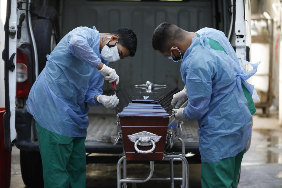 Healthcare workers seal a coffin of a COVID-19 victim patient at Llavallol Dr. Norberto Raúl Piacentini Hospital in Lomas de Zamora, Argentina, Friday, April 23, 2021. Argentina has so far reported more than 67,300 confirmed deaths and more than 3.1 million people sickened by the disease. (AP Photo/Natacha Pisarenko)