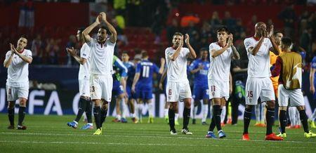 Sevilla players applaud fans after the game