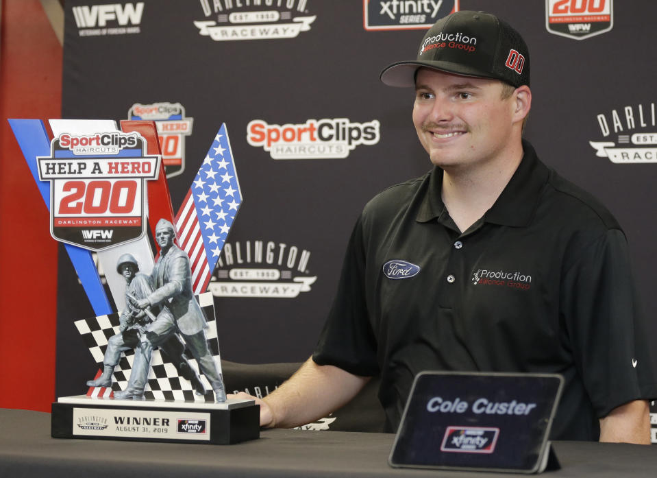 Cole Custer poses with the winner's trophy after Denny Hamlin was disqualified for failing a post-race inspection at the NASCAR Xfinity Series auto race on Saturday, Aug. 31, 2019, at Darlington Raceway in Darlington, S.C. (AP Photo/Terry Renna)