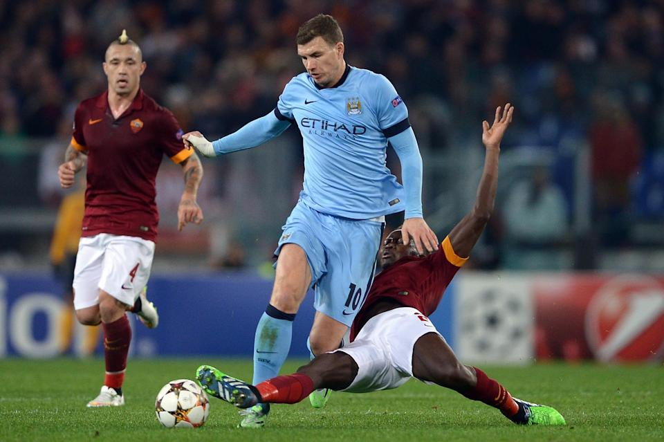 Manchester City's Edin Dzeko is tackled by Roma's Mapou Yanga-Mbiwa during their UEFA Champions League match on December 10, 2014 at the Olympic stadium in Rome (AFP Photo/Filippo Monteforte)