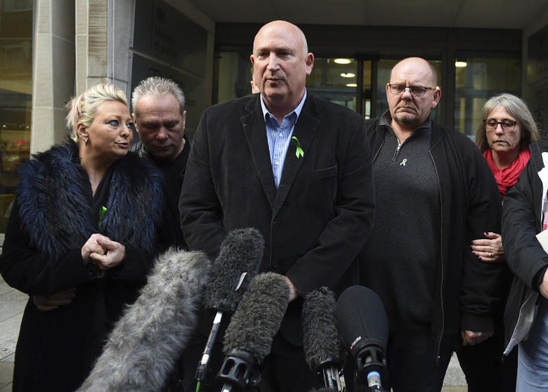 The family of Harry Dunn, from left, mother Charlotte Charles, stepfather Bruce Charles, family spokesman Radd Seiger, father Tim Dunn and stepmother Tracey Dunn speak to the media outside the Ministry Of Justice in London, Friday, Dec. 20, 2019. British prosecutors have charged the wife of an American diplomat over the death of a teenage motorcyclist in a road accident. British police say Harry Dunn died when he was hit by a car driven by Anne Sacoolas, whose husband was stationed at a U.S. military base in England. Sacoolas claimed diplomatic immunity and left Britain after the crash. (David Mirzoeff/PA via AP)