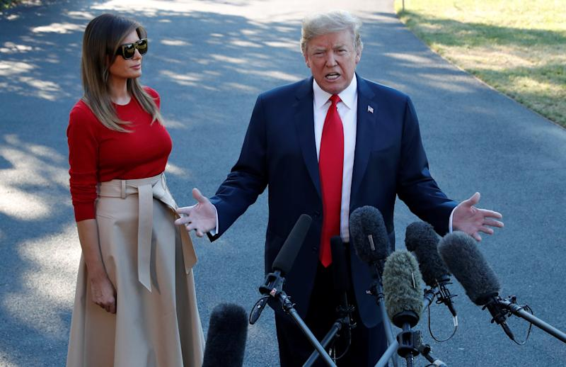 U.S. President Donald Trump speaks with the news media, with first lady Melania Trump standing beside him, before boarding Marine One for travel to Europe from the White House, in Washington, U.S., July 10, 2018. REUTERS/Leah Millis