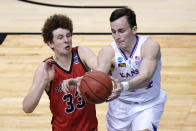 Kansas forward Mitch Lightfoot, left, and Eastern Washington guard Jacob Groves (33) chase a loose ball during the first half of a first-round game in the NCAA college basketball tournament at Farmers Coliseum in Indianapolis, Saturday, March 20, 2021. (AP Photo/AJ Mast)