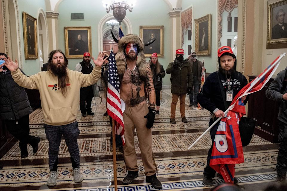 A lawyer for Jacob Chansley (center), the self-described Q Shaman, wants President Donald Trump to pardon his client because he was just following the president's orders. (Photo: SAUL LOEB via Getty Images)