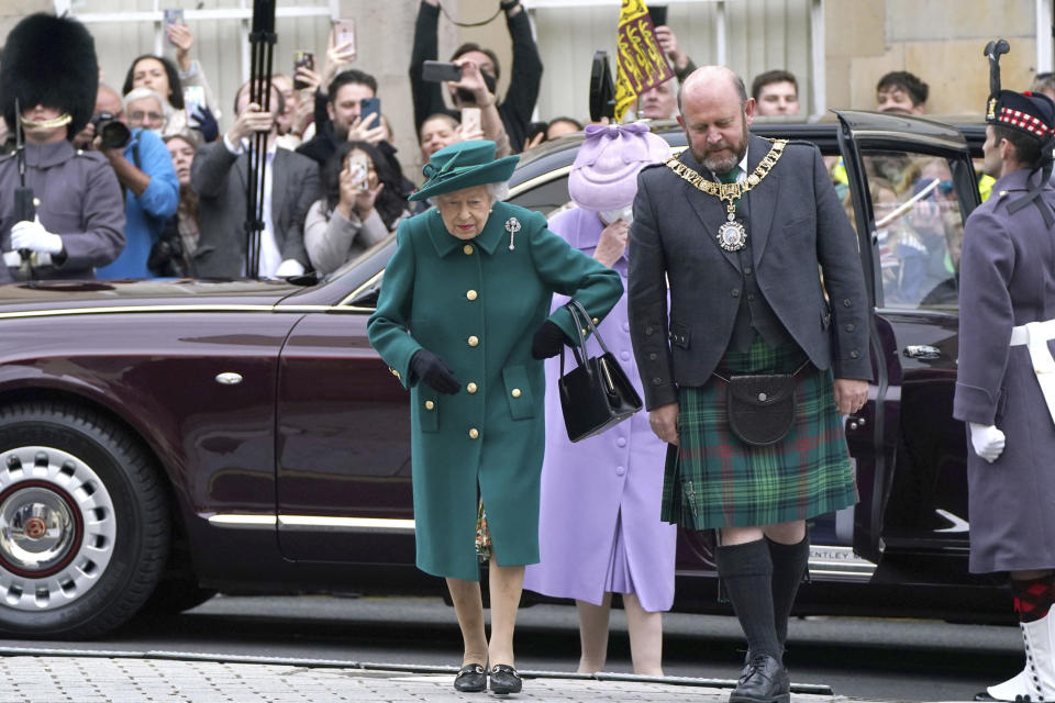 Queen Elizabeth II, center, arrives at the Scottish Parliament in Edinburgh, where she will deliver a speech in the debating chamber to mark the official start of the sixth session of Parliament, in Edingurgh, Scotland, Saturday, Oct. 2, 2021. (Andrew Milligan/via AP)