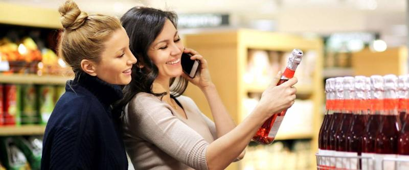Two women choosing a wine, champagne at supermarket