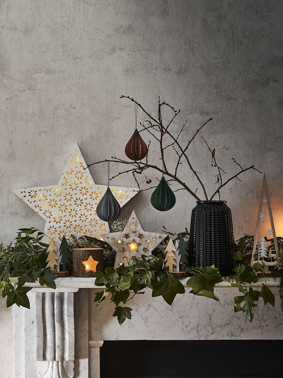 """<p><a href=""""https://www.housebeautiful.com/uk/lifestyle/shopping/g29585316/christmas-garland/"""" rel=""""nofollow noopener"""" target=""""_blank"""" data-ylk=""""slk:Garlands"""" class=""""link rapid-noclick-resp"""">Garlands</a> are a traditional decoration for fireplaces, but that doesn't mean you can't play around with adding other decorations. Dress your mantelpiece to impress this Christmas with mini <a href=""""https://www.housebeautiful.com/uk/lifestyle/shopping/g29471908/twig-christmas-tree/"""" rel=""""nofollow noopener"""" target=""""_blank"""" data-ylk=""""slk:twig trees"""" class=""""link rapid-noclick-resp"""">twig trees</a> (or simply twigs from the garden), glowing tea lights, fresh eucalyptus, paper decorations and your favourite figurines. </p><p><strong>READ MORE</strong>: <a href=""""https://www.housebeautiful.com/uk/lifestyle/shopping/g29585316/christmas-garland/"""" rel=""""nofollow noopener"""" target=""""_blank"""" data-ylk=""""slk:26 Christmas garlands to buy for your home"""" class=""""link rapid-noclick-resp"""">26 Christmas garlands to buy for your home</a></p>"""