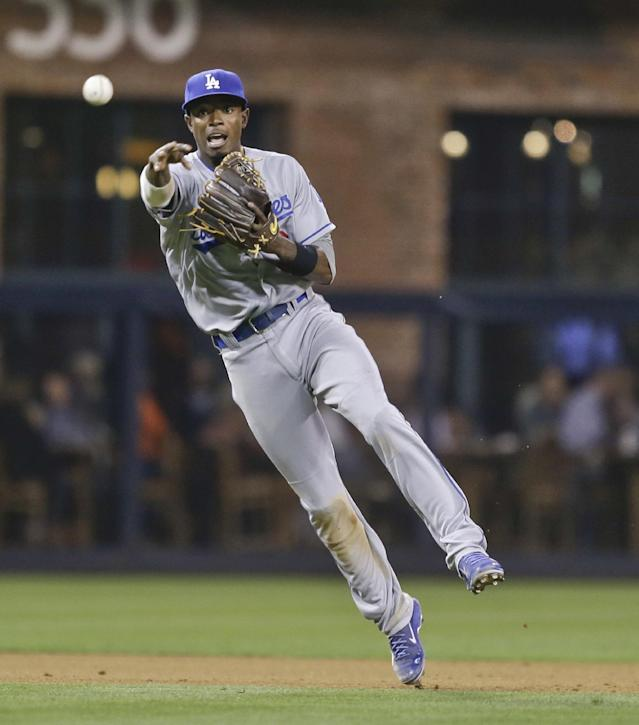 Los Angeles Dodgers shortstop Dee Gordon makes an off-balance throw to get the out on San Diego Padres' Tommy Medica at first base in the fifth inning of a baseball game Friday, Sept. 20, 2013, in San Diego. (AP Photo/Lenny Ignelzi)