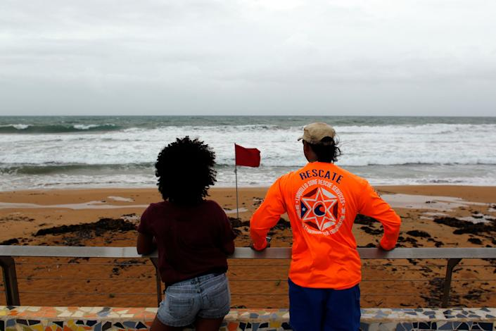 A couple watch from the shore at heavy surf as hurricane Irma approaches Puerto Rico.