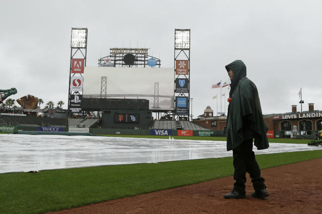 Dave Apelt, with security, looks at rain fall on the tarp-covered infield of Oracle Park before the start of an opening day baseball game between the Tampa Bay Rays and San Francisco Giants Friday, April 5, 2019, in San Francisco. (AP Photo/Eric Risberg)