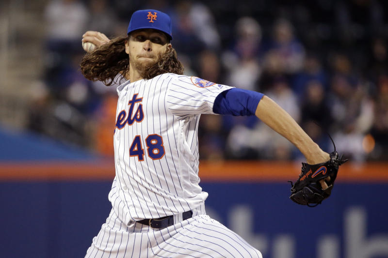 FILE - In this April 5, 2017, file photo, New York Mets starting pitcher Jacob deGrom throws during the first inning of the team's baseball game against the Atlanta Braves in New York. The scoreboard at Citi Field showed deGrom hitting 98 mph that night, and the ballpark buzzed with the Mets star right-hander seemingly back in top form. From watching broadcasts and scoreboards, fans are seeing velocities ramp up around the majors this year. Check the leaderboards at analytics website Fangraphs, and you'll see that last April, pitchers averaged 92.2 mph on four-seam fastballs. Through Thursday's games this season, they're up to 93.1 mph, an unprecedented jump. Did some 300 pitchers all find ways to boost their speed in the offseason? Not quite. More likely, the perceived speed spike is coming from a change in how pitches are being recorded and reported. (AP Photo/Frank Franklin II, File)