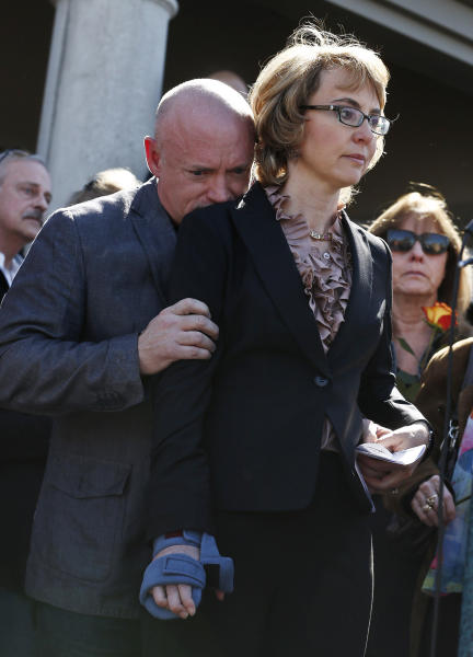 Former Rep. Gabrielle Giffords, right, listens to a speaker as an emotional husband Mark Kelly, left, hugs Giffords during a return to the site of a shooting that left her critically wounded to urge key senators to support expanded background checks for gun purchases, Wednesday, March 6, 2013, in Tucson, Ariz. (AP Photo/Ross D. Franklin)