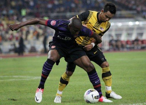 Arsenal's player Benik Afobe (L) fights for the ball with Malaysia's player Aidil Zafuan Razak (R)