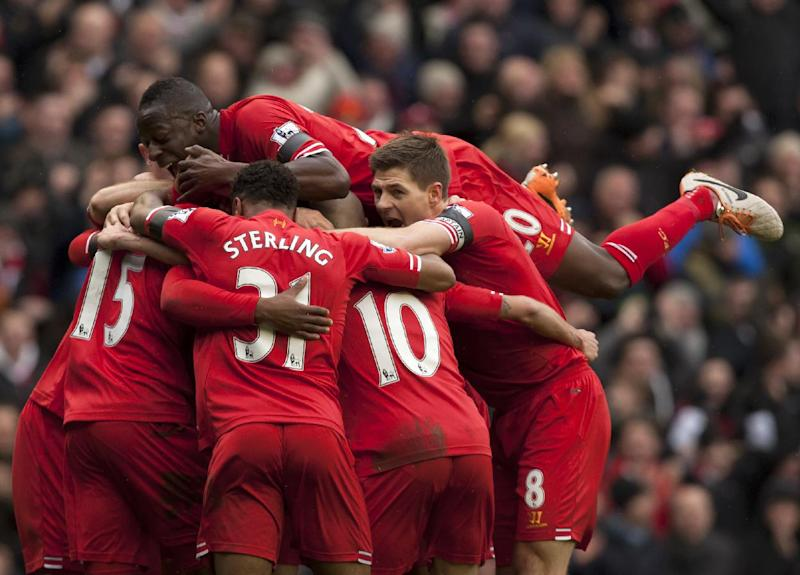 Liverpool's Daniel Sturridge, unseen, is swamped by jubilant teammates as he celebrates scoring his team's fourth goal against Arsenal during their English Premier League soccer match at Anfield Stadium, Liverpool, England, Saturday Feb. 8, 2014. (AP Photo/Jon Super)