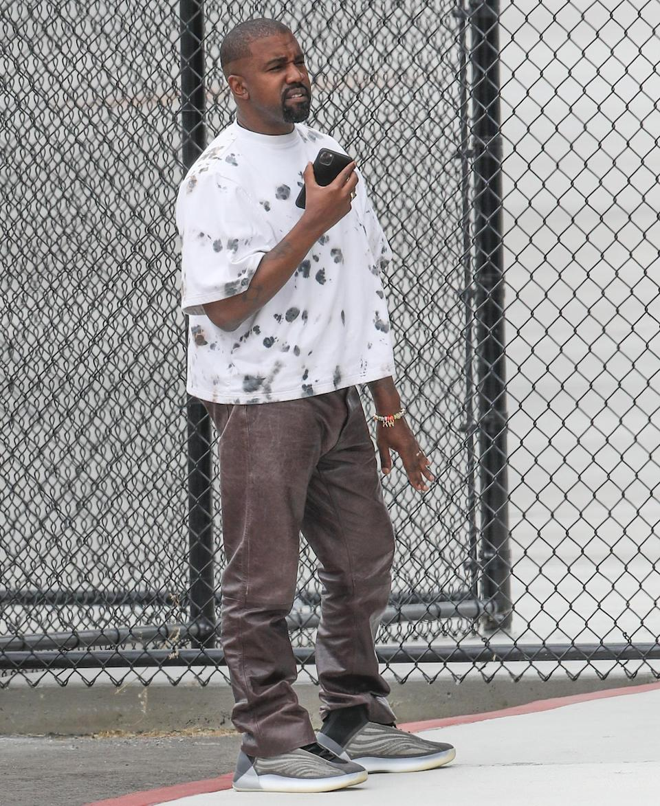 <p>Kanye West grabs a call on Wednesday while at the Van Nuys Airport in Los Angeles. </p>