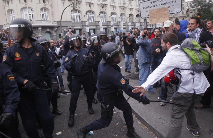 """File - In this Sept. 25, 2012 file photo, a police officer hits a man with a baton during a march to the parliament against austerity measures announced by the Spanish government, in Madrid. Spain's government said Friday Oct. 19, 2012 it is considering a ban on photographing, filming and reproducing images of police and state security forces while """"in the exercise of their functions."""" Deputy Prime Minister Soraya Saenz de Santamaria said that after months of television and internet viewing of sometimes violent clashes between police and demonstrators a balance had to be struck """"between citizens' right to protest"""" and a need """"to uphold the integrity of state security forces."""" (AP Photo / Andres Kudacki, File)"""