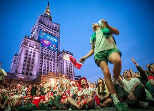Polish football fans cheer and shout in the Warsaw Fanzone in June