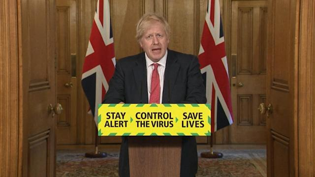 Boris Johnson delivers a media briefing , fronted by the government's new slogan. (COVID-19).