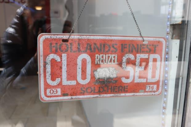A closed sign hangs in the window of Barbier les Rois in Quebec City. The shop has closed and reopened three times in the past year, as the region has moved in and out of the red COVID-19 alert category.